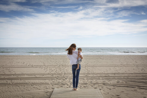 Rear view of mid adult woman carrying toddler daughter on beach, Castelldefels, Catalonia, Spain - CUF26058