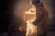 Worker raking molten steel in foundry - CUF26079