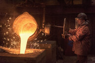 Worker pouring molten metal from flask in foundry workshop - CUF26085