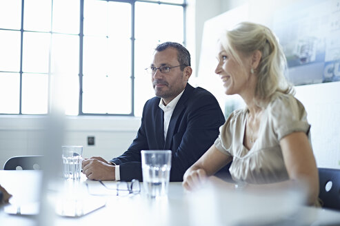 Businesswoman and man at conference table in office meeting - CUF26157