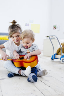 Brother and sister playing toy guitar at home - CUF26199