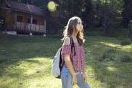 Young woman gazing from forest glade, Sattelbergalm, Tyrol, Austria - CUF26265