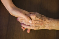 Close up of mid adult woman and her grandmother holding hands - CUF26415