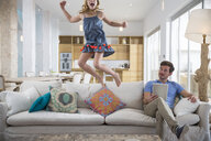 Girl jumping mid air from living room sofa whilst father uses digital tablet - CUF26436