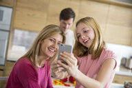 Mid adult woman and daughter taking smartphone selfie in dining room - CUF26439
