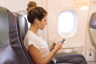 Young woman on airplane choosing music on smartphone - CUF26508