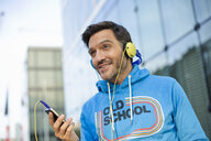 Smiling mature man choosing headphone music on smartphone - CUF26559