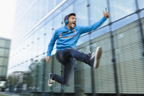 Mature man with headphones and smartphone jumping mid air on street - CUF26562