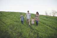 Parents with son and daughter strolling in grassy field - CUF26592