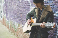 Musician playing guitar by canal wall, Milan, Italy - CUF26625