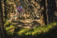 Young male mountain biker jumping over rock formation in forest - CUF26667