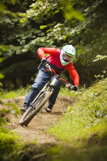 Young woman downhill mountain biking in forest - CUF26673