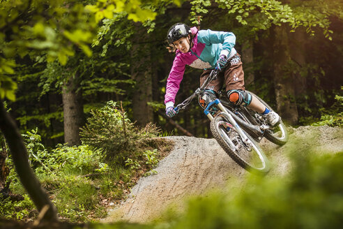 Young female mountain biker jumping on forest track - CUF26679