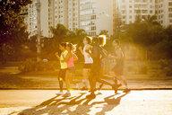 Six adult friends doing training run in park - CUF26757