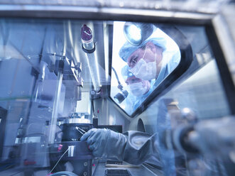 Electronics workers looking into sealed work station window in clean room laboratory - CUF27015