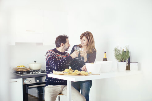 Mature couple toasting and preparing food in kitchen - CUF27045
