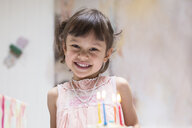 Portrait of happy little girl with burning candles on birthday cake - DRF01740