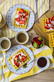 Two plates of waffles garnished with strawberries, Greek yogurt and almonds on breakfast table - GIOF03958