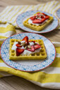 Waffle garnished with strawberries, Greek yogurt and almonds on plate - GIOF03961