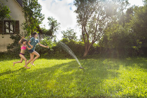 Girl and her little sister having fun with lawn sprinkler in the garden - LVF07056