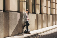 Young city businessman leaning against office building reading smartphone text - CUF27119