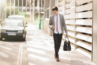 Young city businessman reading smartphone texts whilst walking outside office - CUF27128