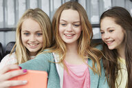 Three girls posing for smartphone selfie in shelter - CUF27143