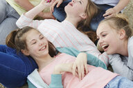 Cropped view of five boys and girls lying on ground - CUF27155