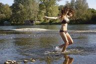 Young woman wearing a bikini splashing and playing in river - CUF27158