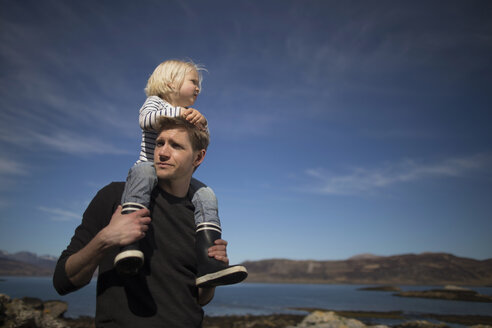 Father carrying son on shoulders, Loch Eishort, Isle of Skye, Hebrides, Scotland - CUF27335