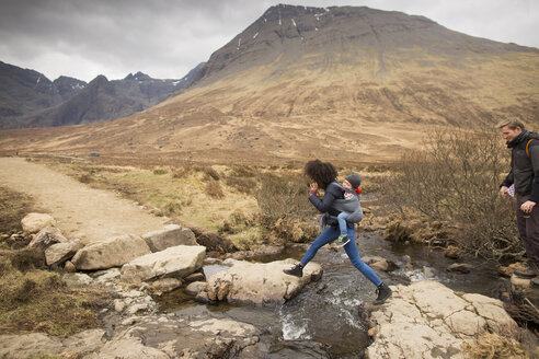 Woman leaping over stream, Fairy Pools, near Glenbrittle, Isle of Skye, Hebrides, Scotland - CUF27338