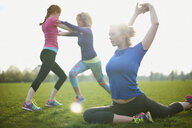 Three women exercising and stretching in the park - CUF27362