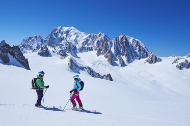 Female and male skiers talking on Mont Blanc massif, Graian Alps, France - CUF27416