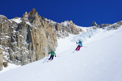Male and female skiers skiing down Mont Blanc massif, Graian Alps, France - CUF27431