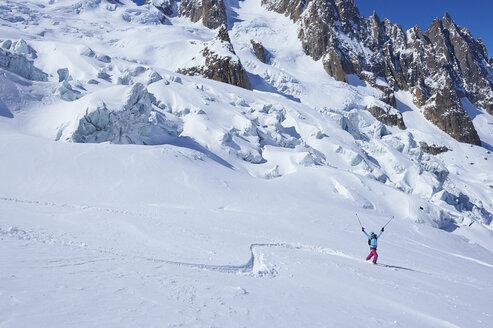 Mature female skier celebrating on Mont Blanc massif, Graian Alps, France - CUF27434