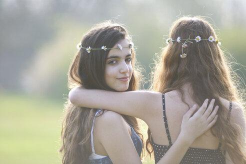 Rear view portrait of two teenage girls wearing daisy chain headdresses in park - CUF27467