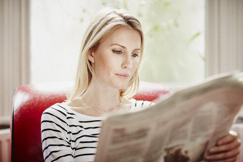 Mid adult woman reading newspaper - CUF27683