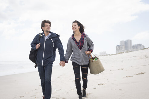 Romantic young couple strolling on windswept beach, Western Cape, South Africa - CUF27716