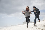 Young couple running and chasing on beach, Western Cape, South Africa - CUF27725