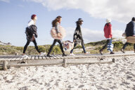 Young adult friends on the move on beach boardwalk, Western Cape, South Africa - CUF27728