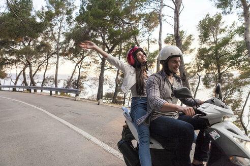 Couples riding moped on rural road, Split, Dalmatia, Croatia - CUF27767