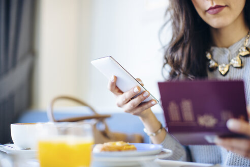 Cropped shot of young woman with digital tablet electronically checking in whilst having breakfast at  boutique hotel in Italy - CUF27797