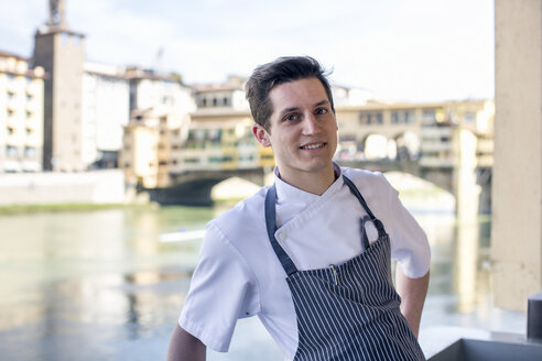 Portrait of young male chef  in front of Ponte Vecchio, Florence, Italy - CUF27809