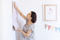 Pregnant mid adult woman holding up pink wallpaper in childs nursery - CUF27821