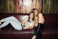 Two adult female friends reclining on sofa on night out in bar - CUF27824