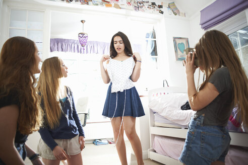Teenage girl photographing friends using instant camera in bedroom - CUF28115