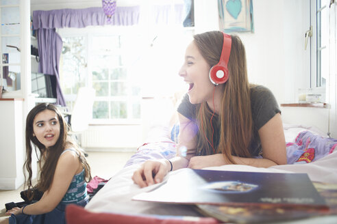 Teenage girl chatting to friend whilst listening to headphones in bedroom - CUF28118