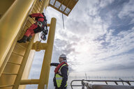 Engineer climbing wind turbine at offshore windfarm - CUF28187