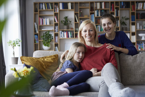 Mother and her daughters cuddling and having fun, sitting on couch - RBF06248