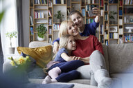 Mother and her daughters sitting on couch,taking smartphone selfies - RBF06251